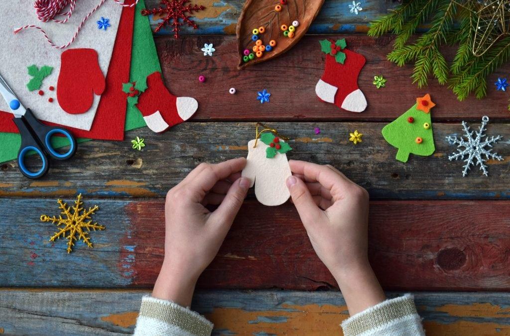 Child making handmade Christmas ornaments for the Christmas tree.