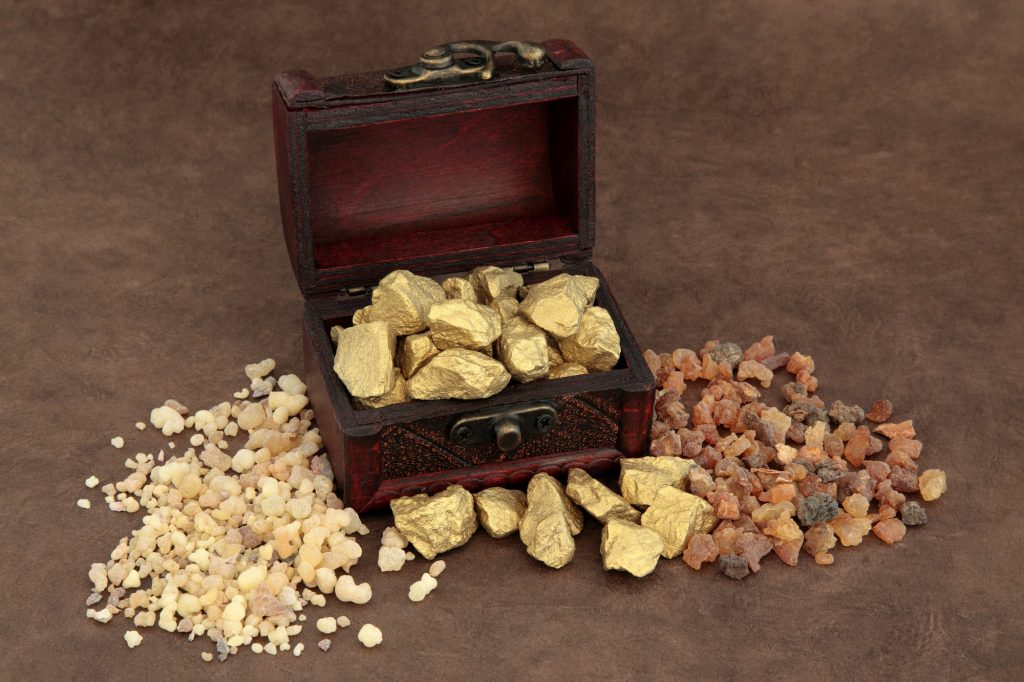 Gold in an old wooden box, frankincense and myrrh lying on each side of the box