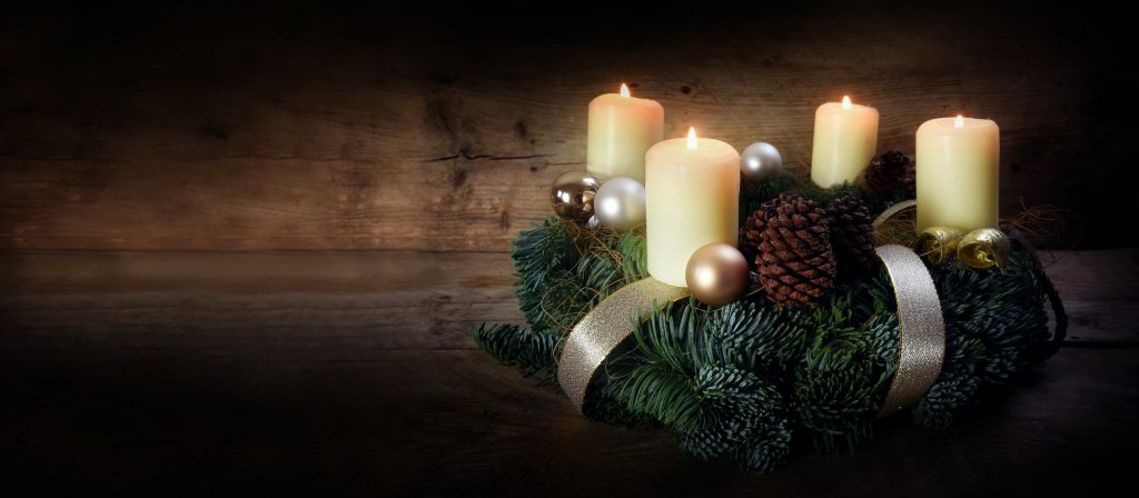 Advent wreath with four white candles and Christmas decoration such as pinecones, glas balls and gold ribbons