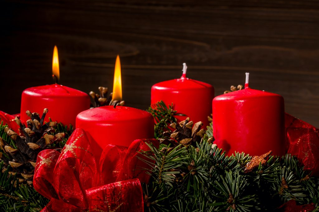 Advent wreath with red candles and red and gold ribbon bows