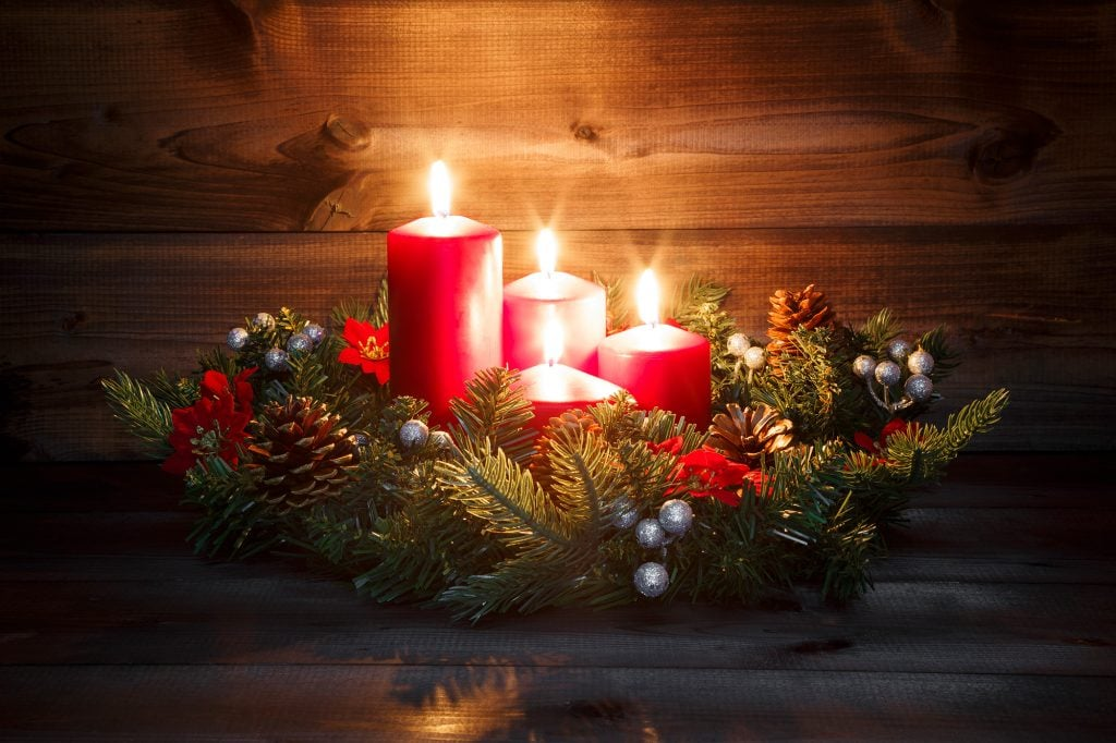 Advent wreath with four red burning candles on a wooden background