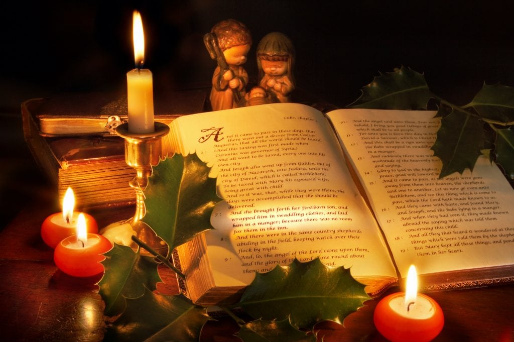 The Bible open with the story of the Birth of Christ showing, lit candles and mistletoe and a small figurine of Joseph, Mary and Baby Jesus