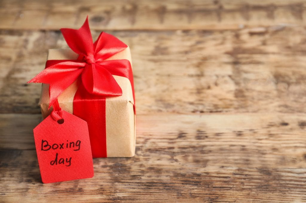 Gift box with a red bow and a small red sign with the writing Boxing Day  standing on a rustik wooden table