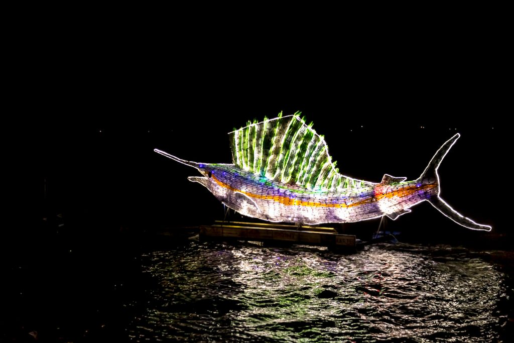 Swordfish made from recycled plastic bottles lit up in many different colors at night on the water