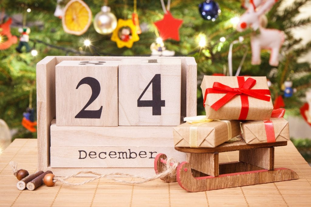 Date 24 December on cube calendar, wrapped gifts with ribbons and christmas tree with lights and decorations.