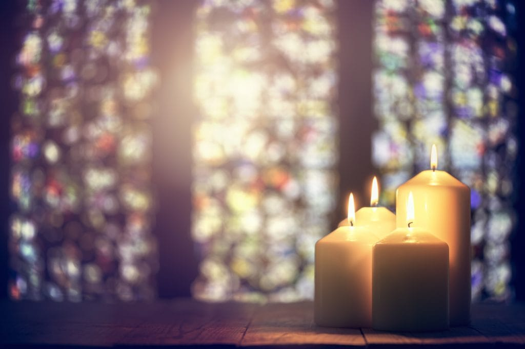 Four white candles burning in a church with multi color glass windows in the background.