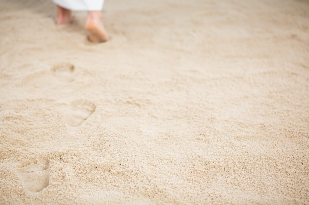 Person walking and leaving footrpints in sand.