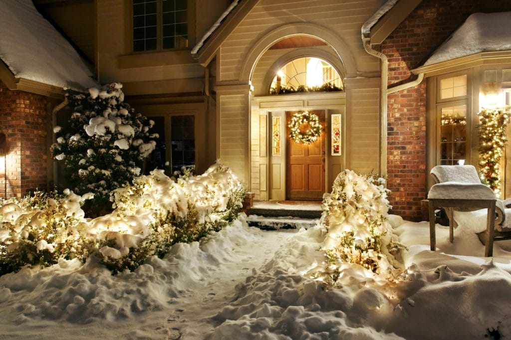 Outside Christmas lights line path to a front door with a Christmas wrath
