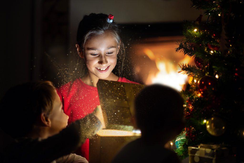 Little girl joyfully smiling as she opens her Christmas present