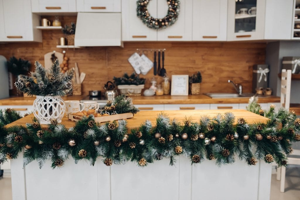 White kitchen with Christmas decorations in green and gold colors.