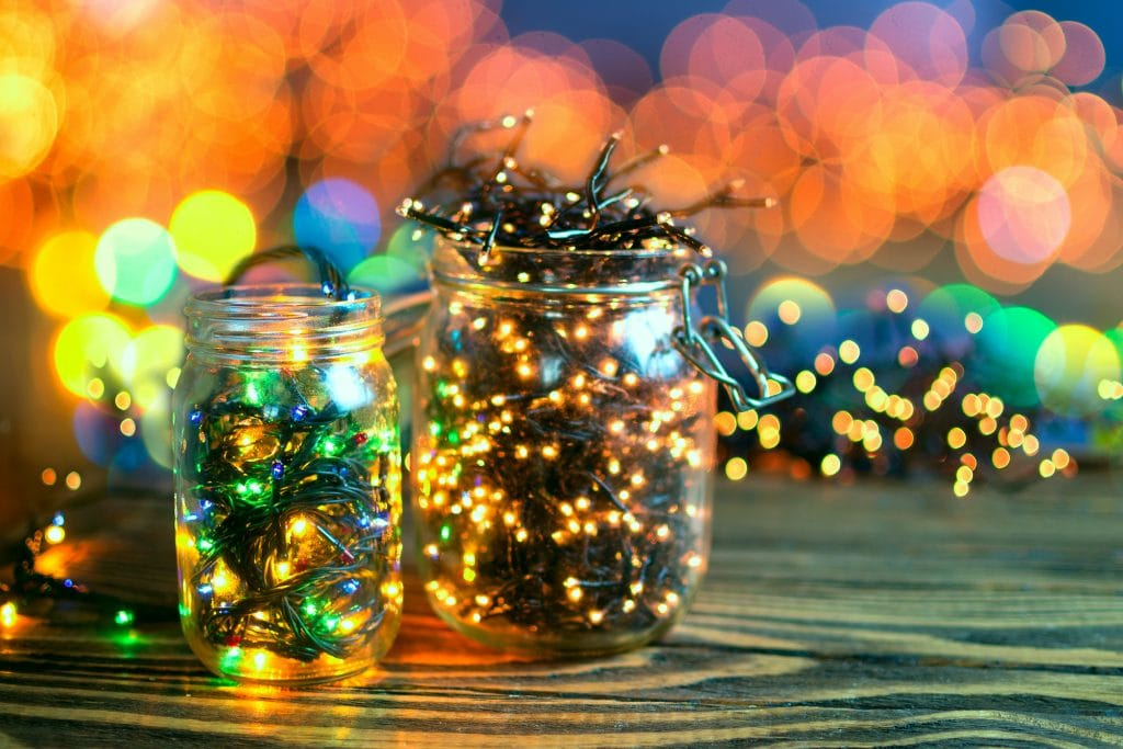 Two jars on a wooden table with Christmas lights in them. The small jar has colored lights in it and the big jar has soft yellow lights.