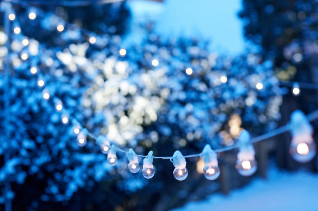Strands of glowing white party lights in snow covered garden