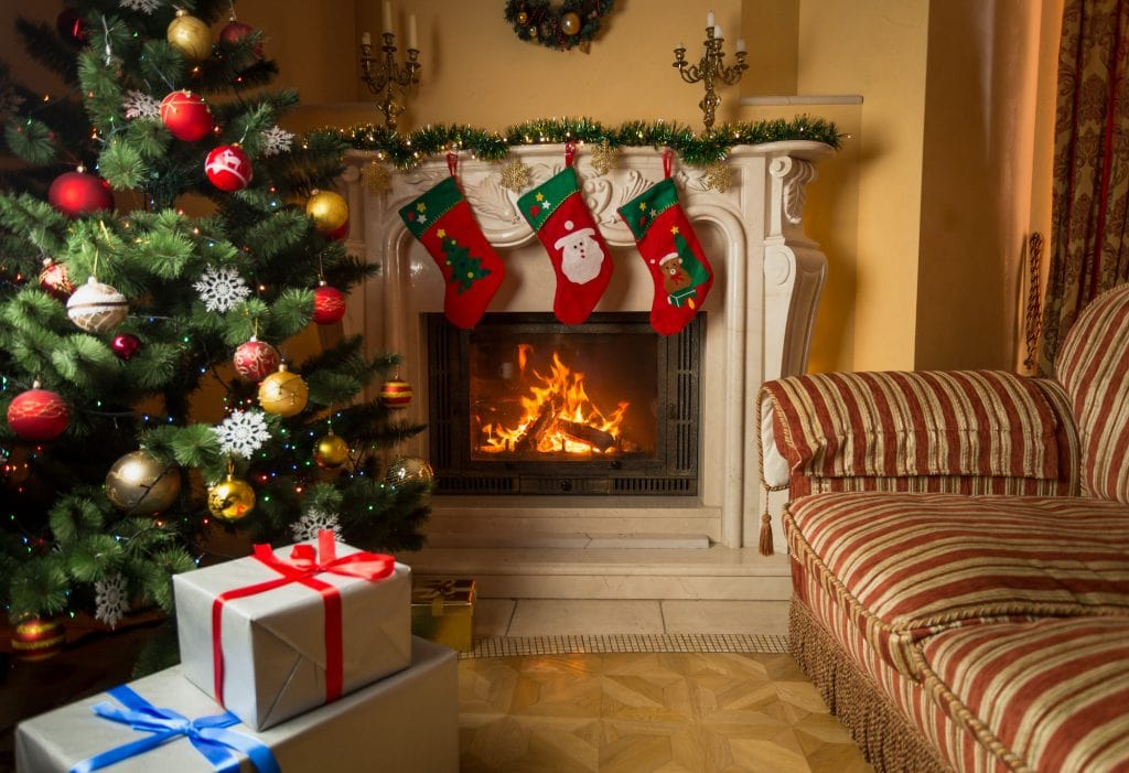 Living room with burning fireplace, decorated Christmas tree and Christmas stockings hanging on the mantel.
