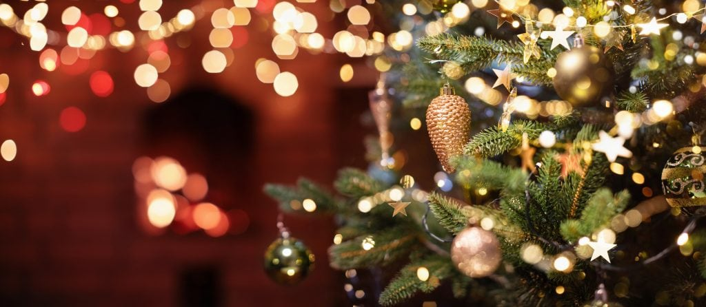 Up close picture of a Christmas Tree with Decorations with a Fireplace in the background