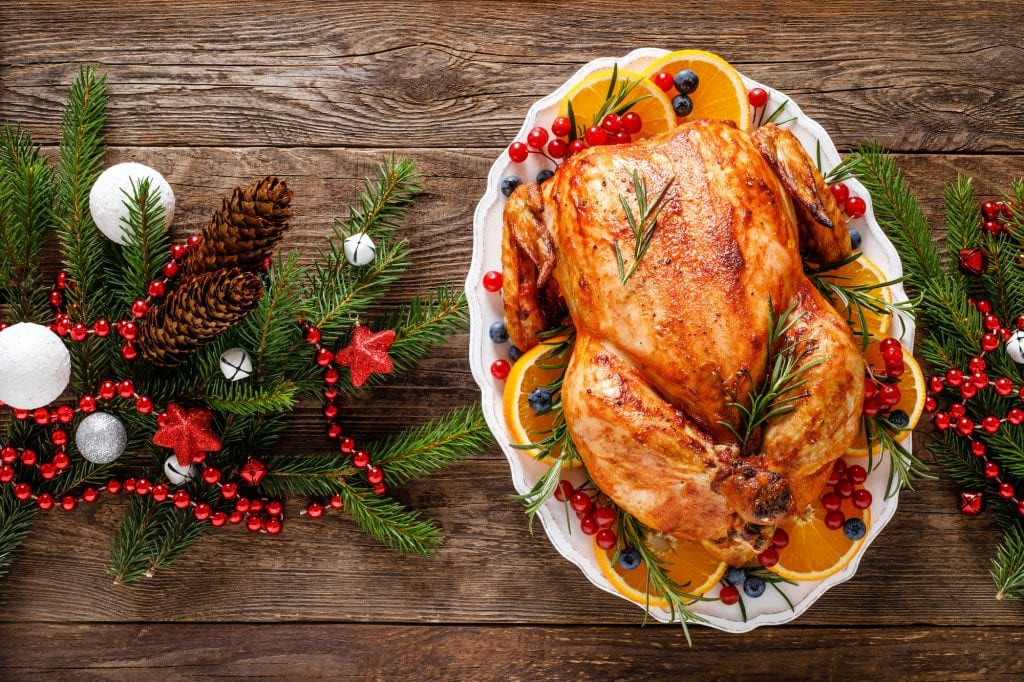 Roasted Christmas turkey on a wooden table.