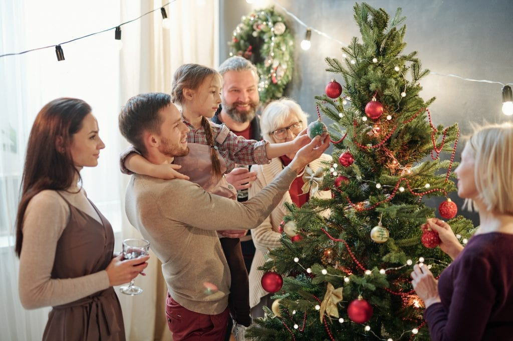 Young man with his little daughter and other family members standing by the Christmas tree.
