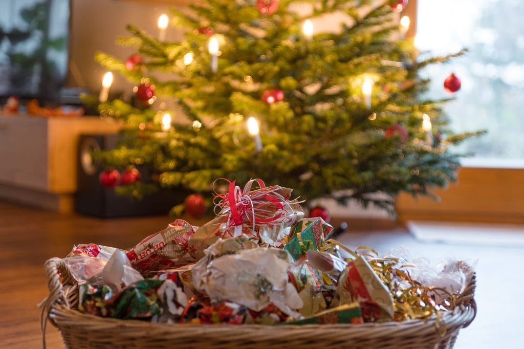 Wrapping paper scraps in basket in front of Christmas tree