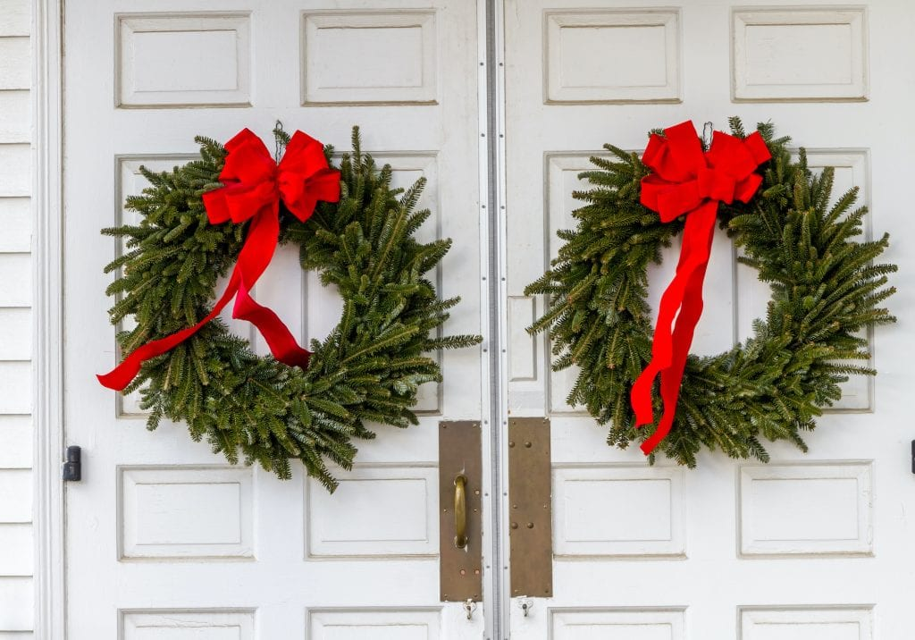 Two evergreen wreaths with red bows on white church doors.