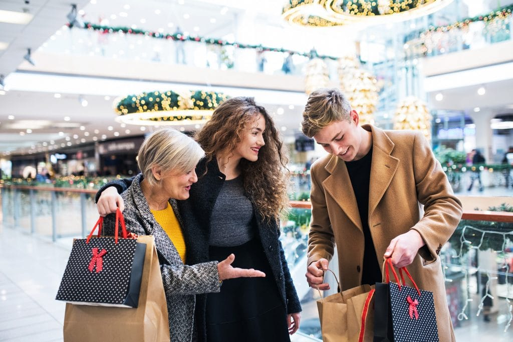 Grandmother and teenage grandchildren in shopping center at Christmas