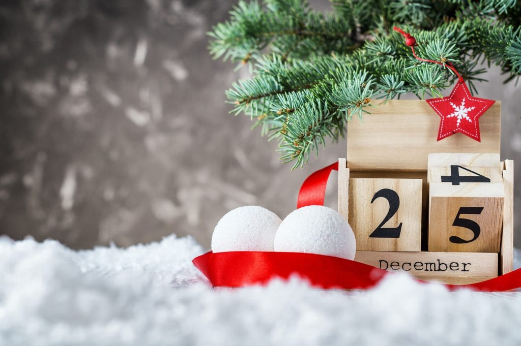 Wooden calendar flipped from 24 to 25 December with snowballs and red ribbon on snow on gray background