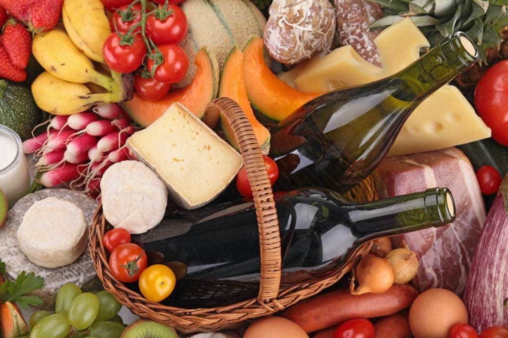 Close up of a basket with fresh fruit, cheese, wine, sausage, meat and vegetables.
