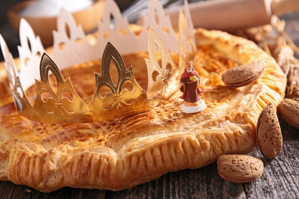 French Galette des rois cake with paper crown, small porcelain figuring and almonds in the shell, on a rustik wooden table