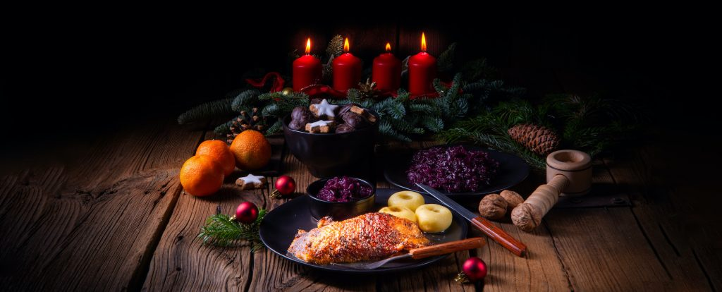 German Christmas feast with roasted goose with baked apples, red cabbage and dumplings on a rustic dark wooden table with a advent wreath in the background