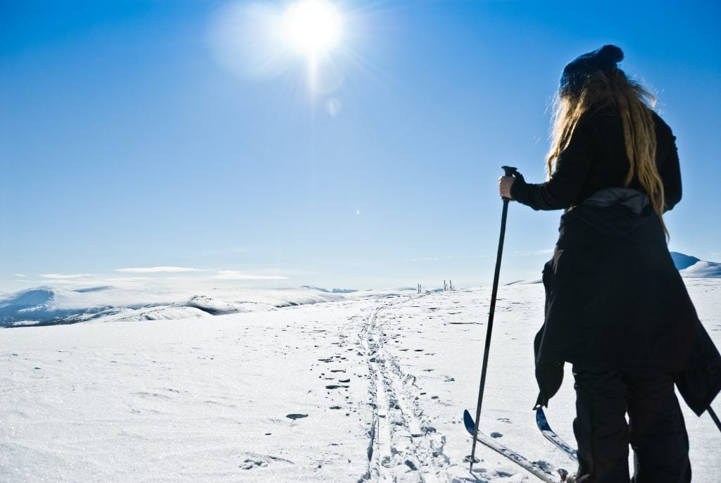 Young lady cross country skiing, on a beautiful winter day with clear blue sky in Oppdal, Norway.