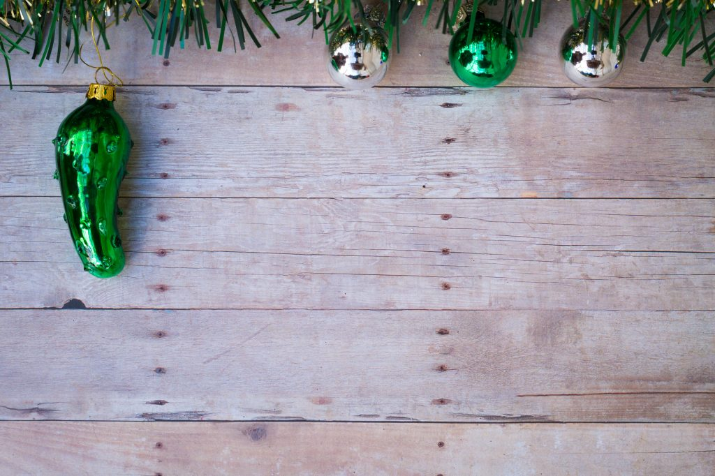 Dark green glass pickle ornament on a wooden background.