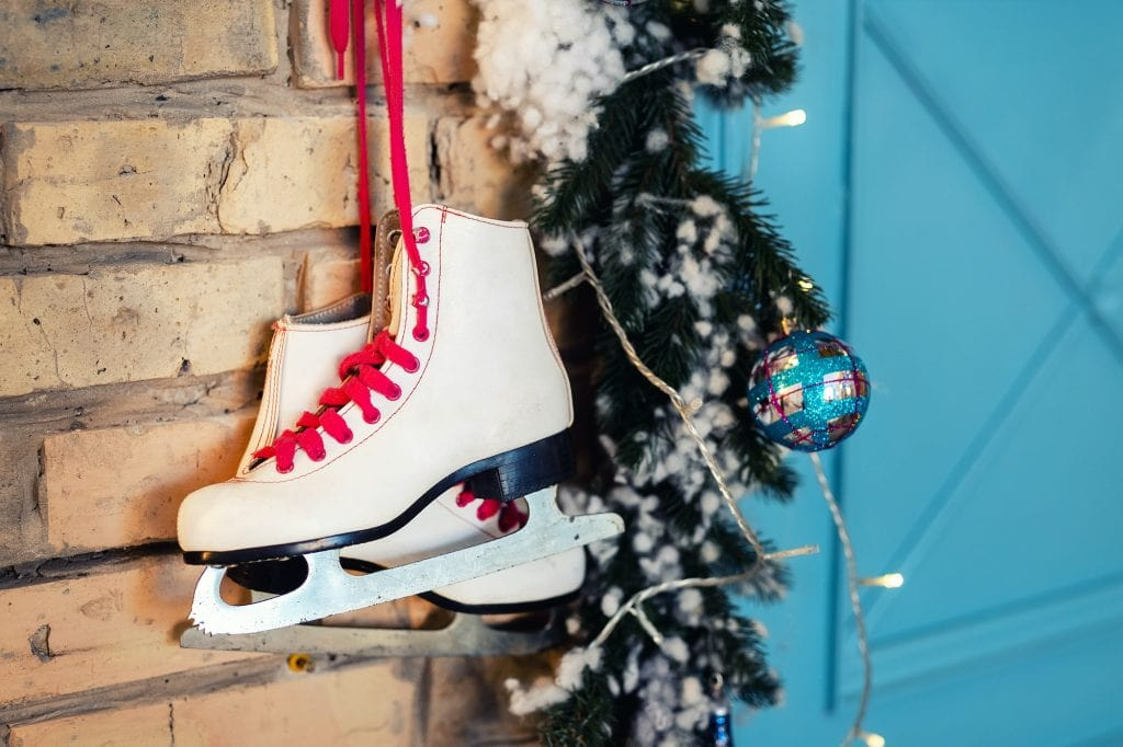 Pair of white vintage leather skates with red laces hanging on old rustic brick wall with garland lights with Christmas tree decoration.