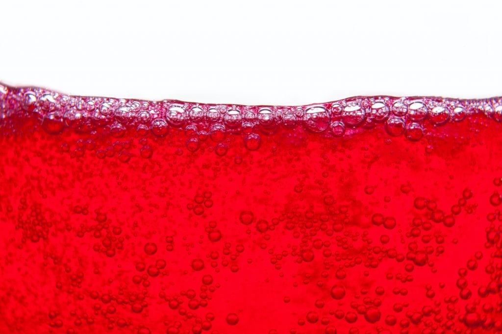 Close up of red julebrus in a glass splashing with bubbles.