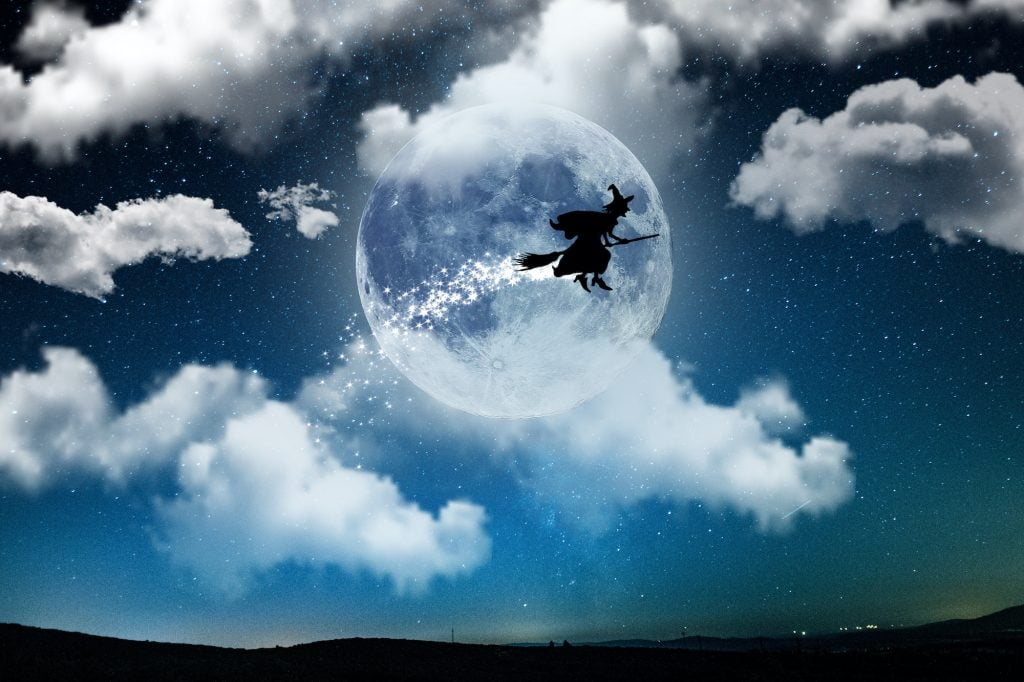 Silhouette of La Befana flying on a broom at night with a full moon as background