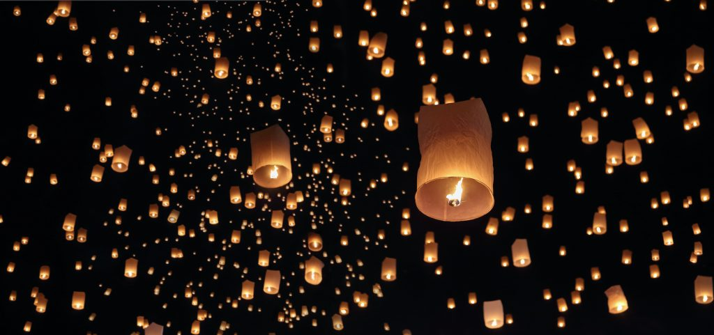 Sky lanterns flying up in the air at night.