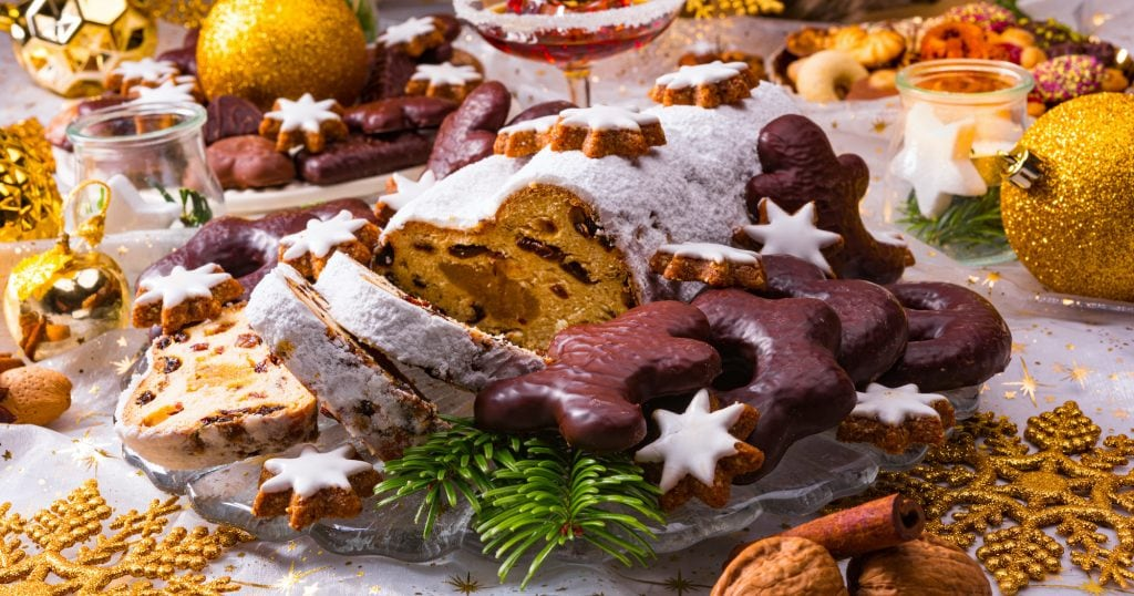 Christmas marzipan stollen and lebkuchen on a glass plate on a table with christmas decoration around it