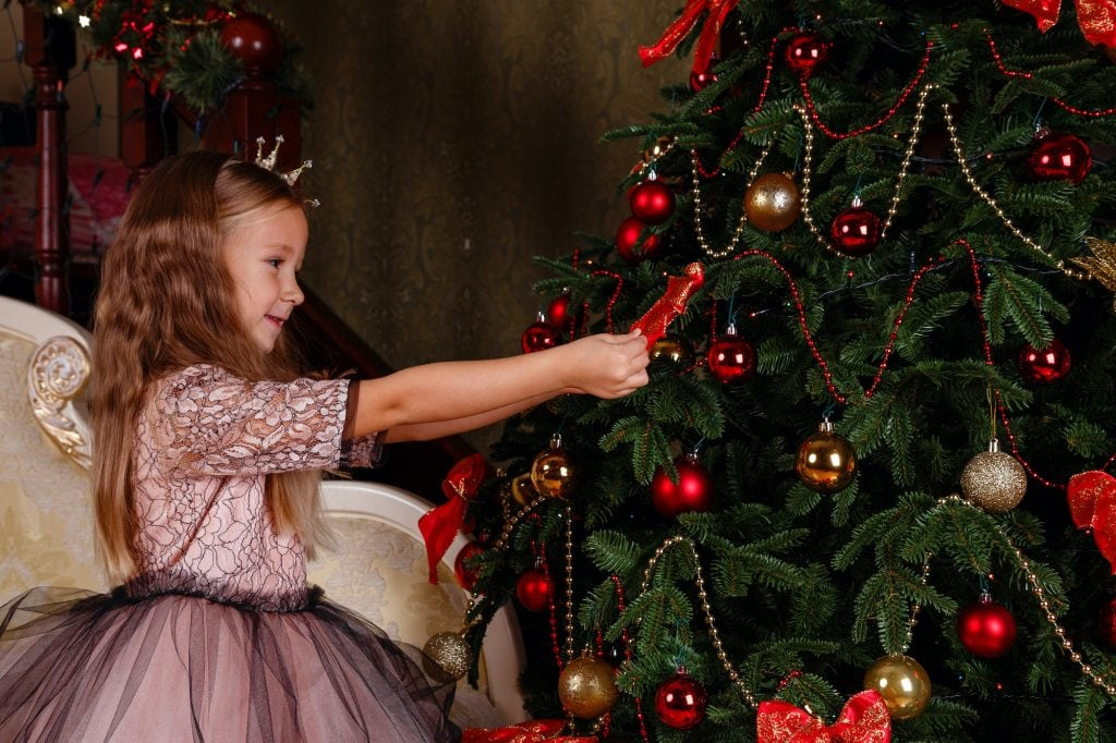 Little girl in a dress as a princess with a crown, standing next to a Christmas tree.