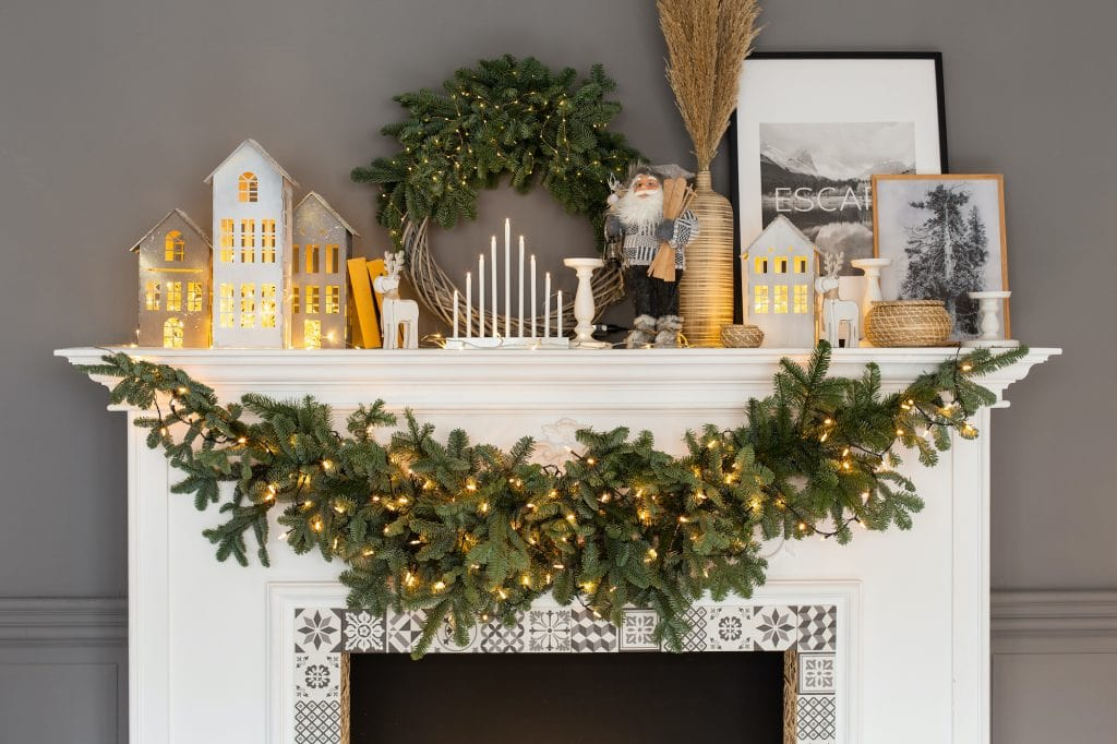 Mantel with Christmas decorations in white, grey and green colors.