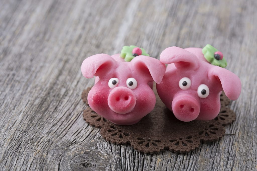 Two Marzipan pigs on wooden background.