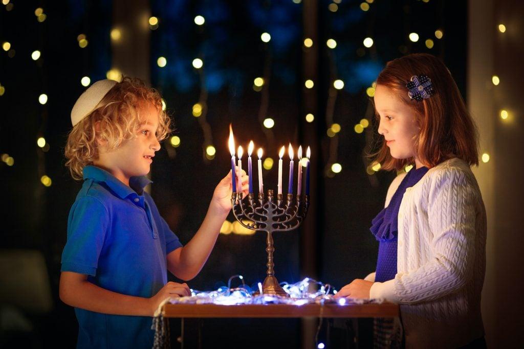 Two children lighting candles on traditional menorah. The boy in kippah with dreidel and Sufganiyah doughnut