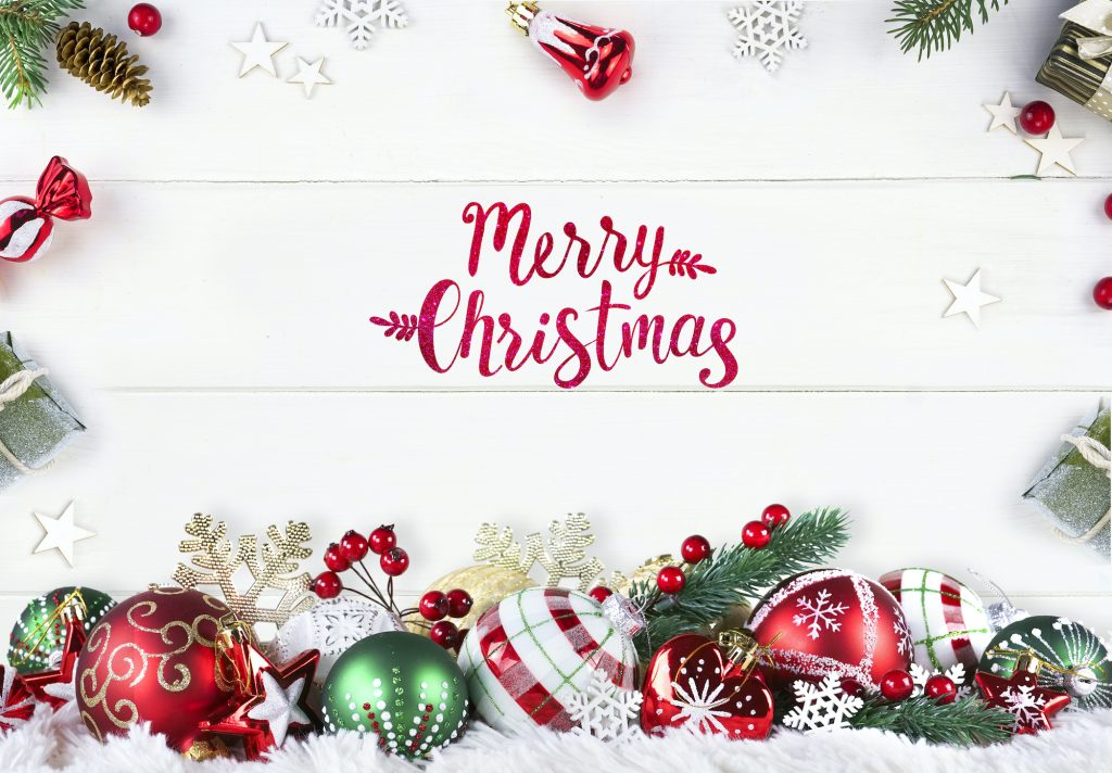 Christmas composition of green and red Christmas balls on white wooden boards with fir branches, gifts and inscription on the floor saying Merry Christmas written in red