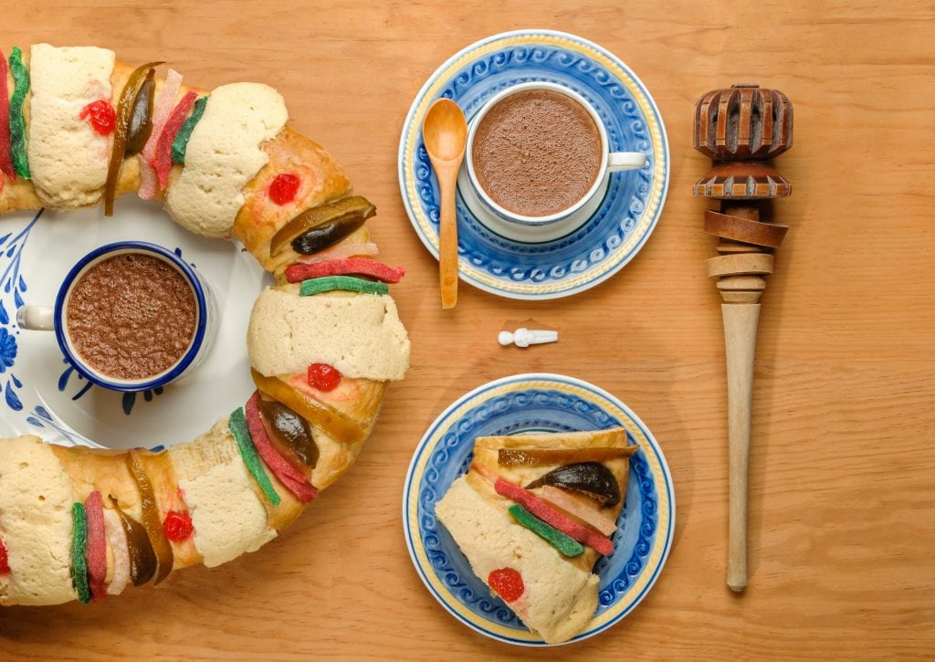 Slice of Epiphany cake with a cup of hot Chocolate and molinillo on a wooden table