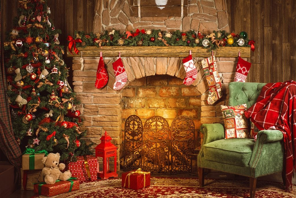 Christmas room with fireplace, armchair and Christmas tree with gifts
