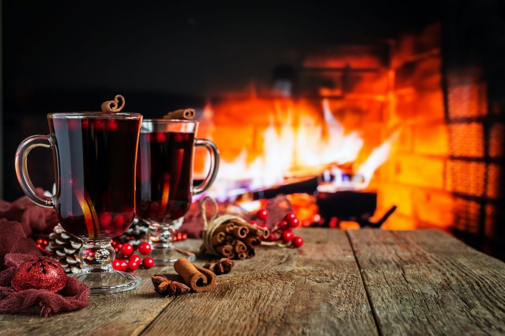 Hot mulled wine in a glass with orange slices, anise and cinnamon sticks on vintage wood table, fireplace as background