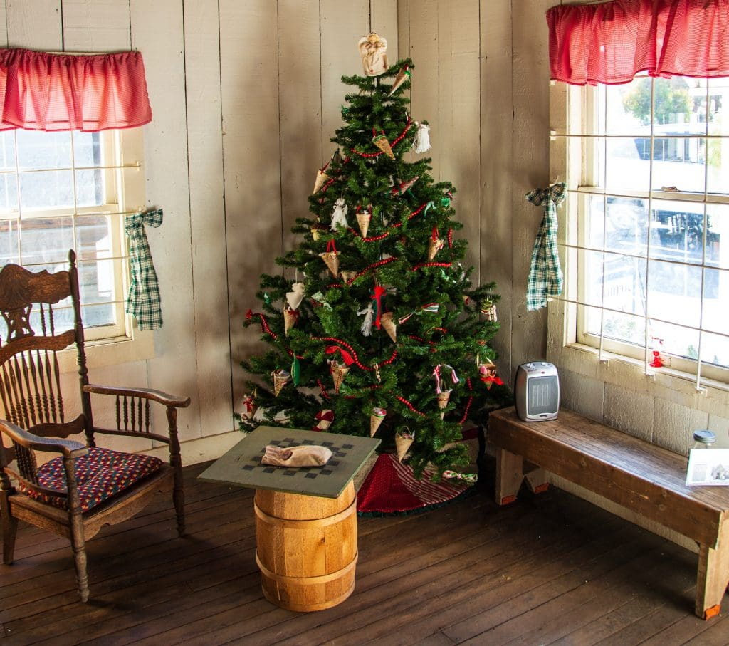 Old fashion Christmas tree standing in a wooden house in the country.