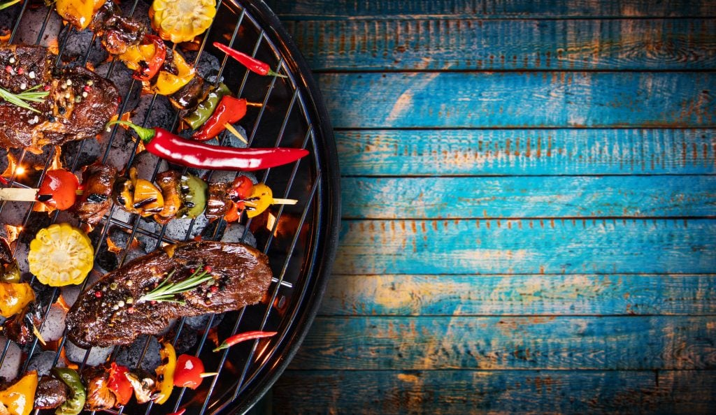Barbecue garden grill with beef steaks and different vegetables.