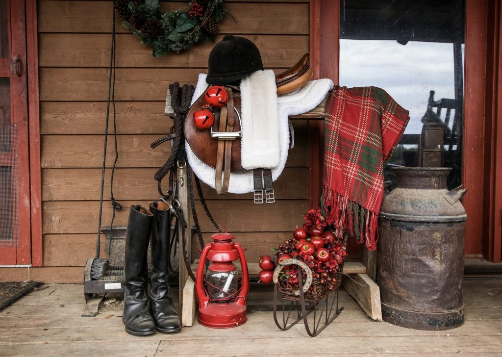 Farmhouse porch decorated with a saddle rack with English tack including saddle, bridle, riding boots decorated for Christmas- bells, lantern and plaid.