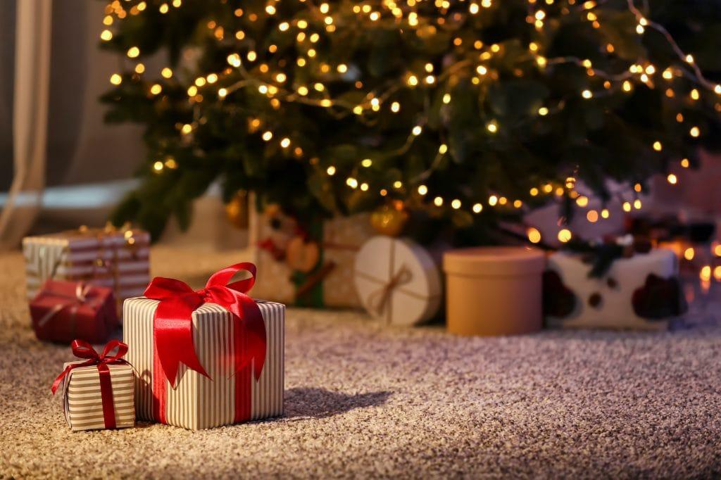 Christmas gift boxes on floor near fir Christmast tree.