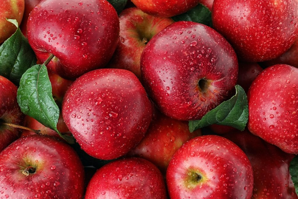 Ripe juicy red apples covered with water drops.