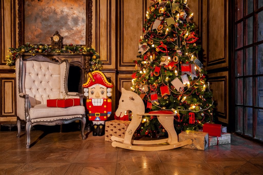 Christmas decoration in grunge room interior with fireplace, rocking horse, kids chair, Christmas tree with presents and a large nutcracker.