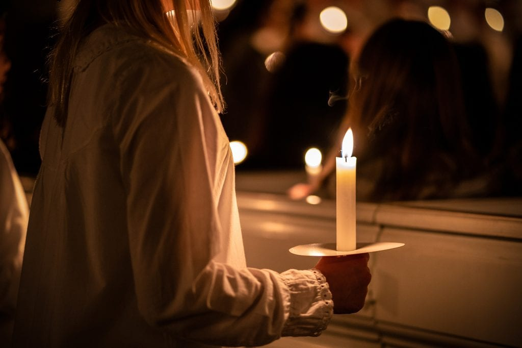 Danish girl holding lit candle in hand during Santa Lucia Day at Christmas