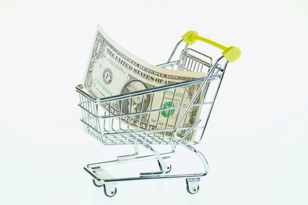 American one dollar bill in a tiny shopping cart with white background
